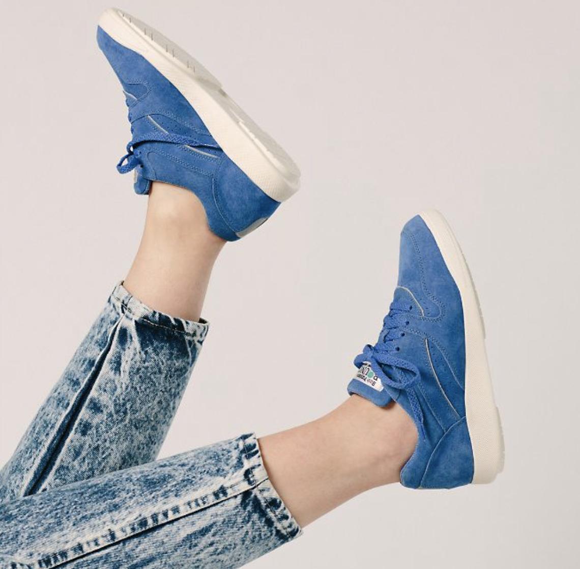 model wears velvet blue walking sneakers with acid wash jeans
