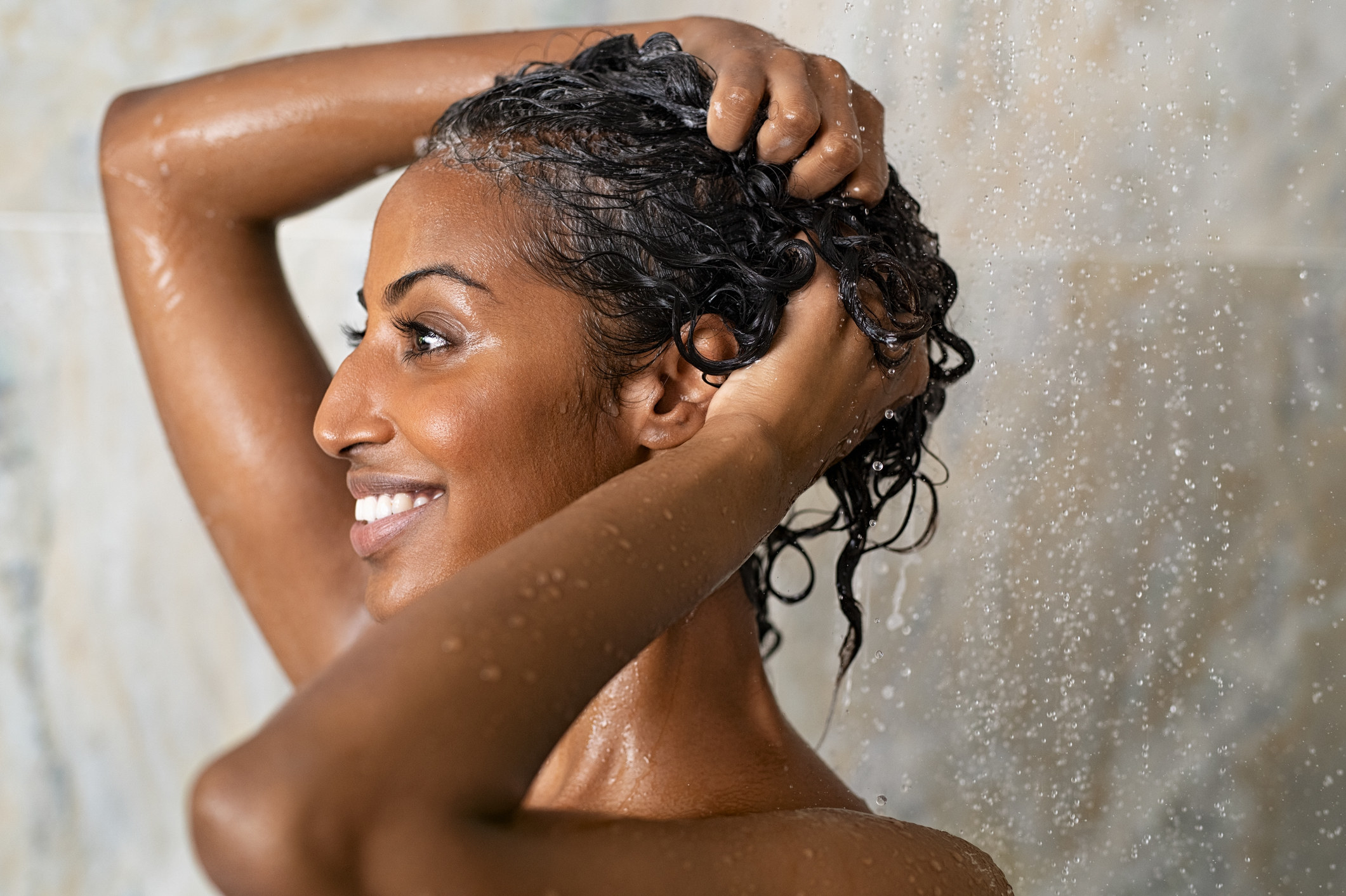 Woman washing hair showering in bathroom at home.