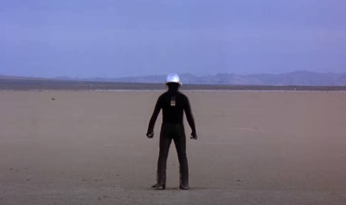 One of the members of daft punk standing alone in a desert