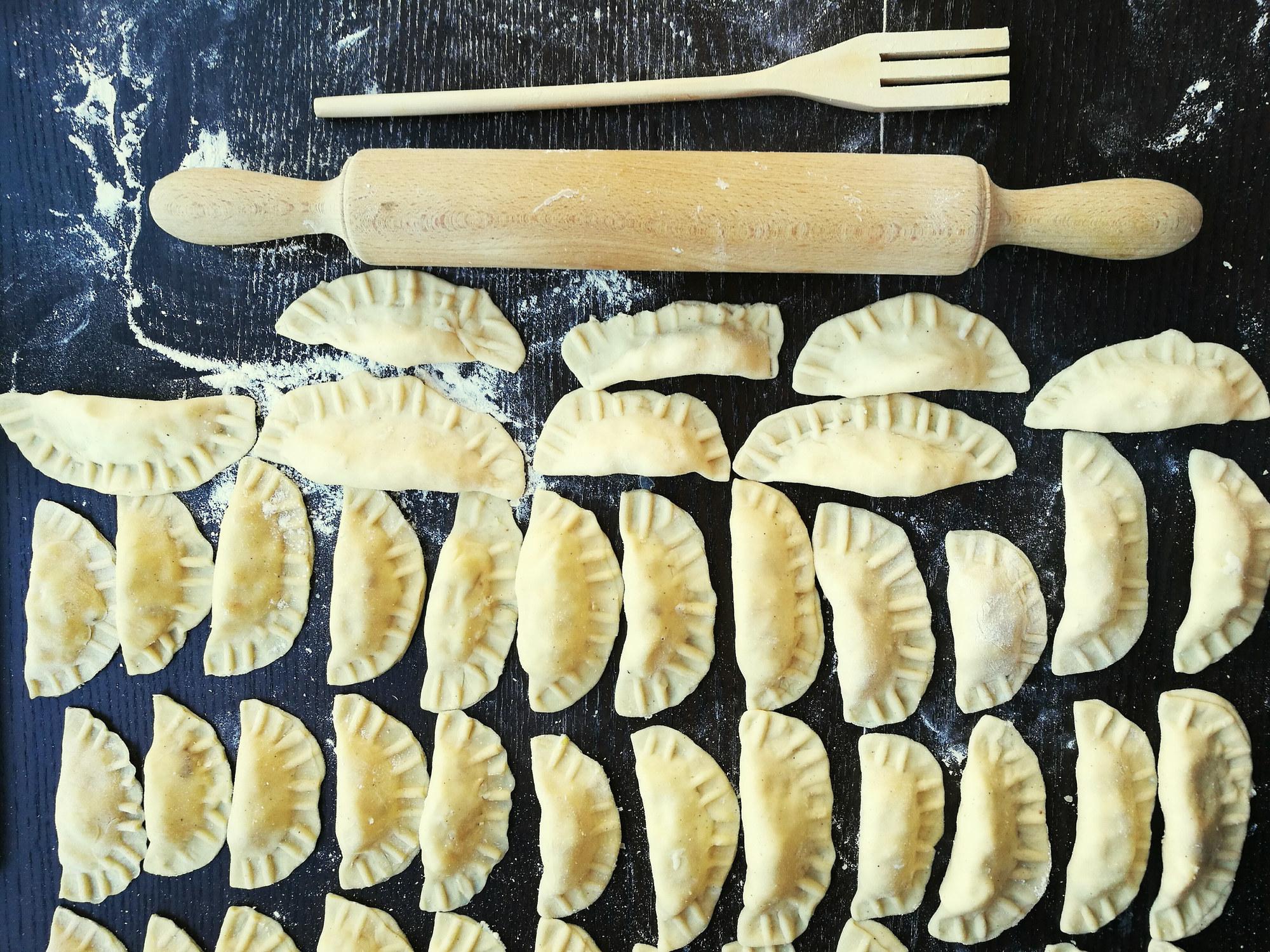 A tabletop of uncooked pierogis aka Polish dumplings.