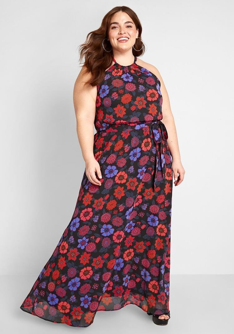 a model in a long black dress with red, blue, and burgundy flowers