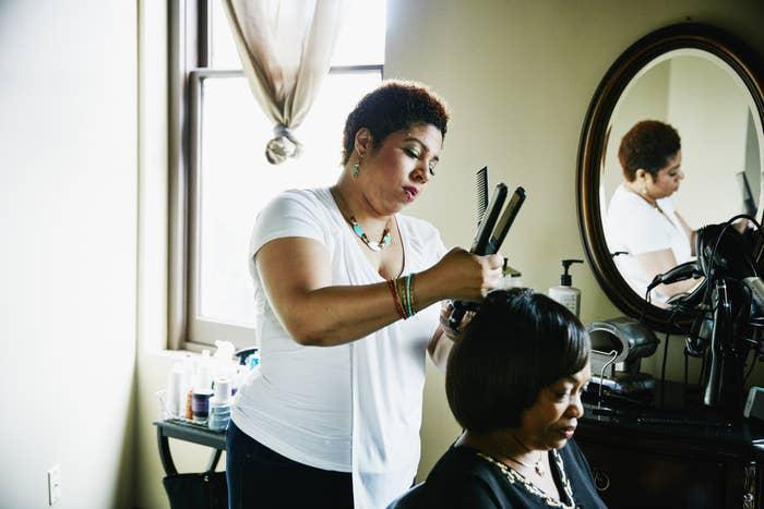 Female salon owner straightening hair of female client in salon