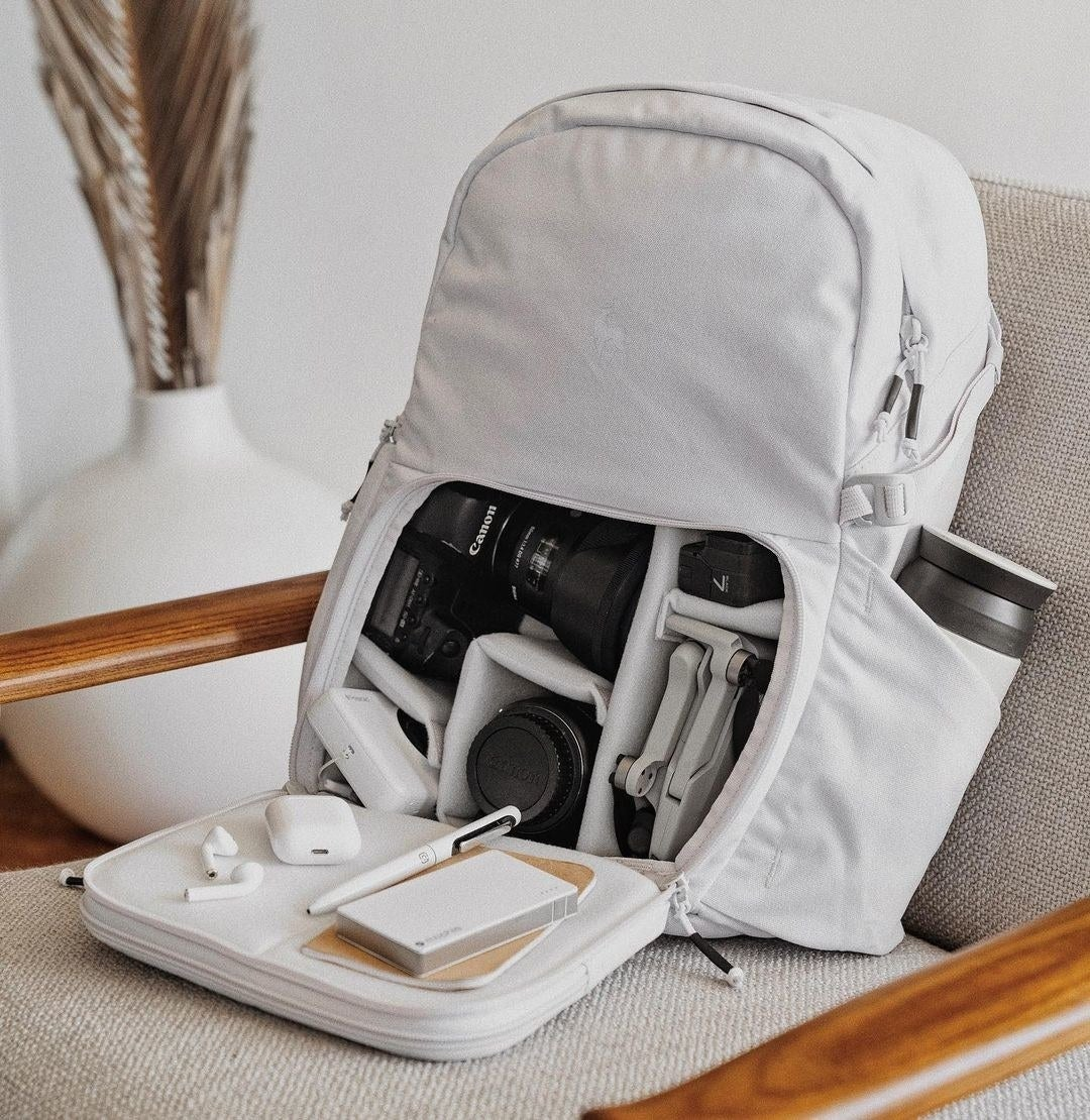 the backpack in white with the front zipper pocket open, showing all the different compartments inside that fit different camera equipment
