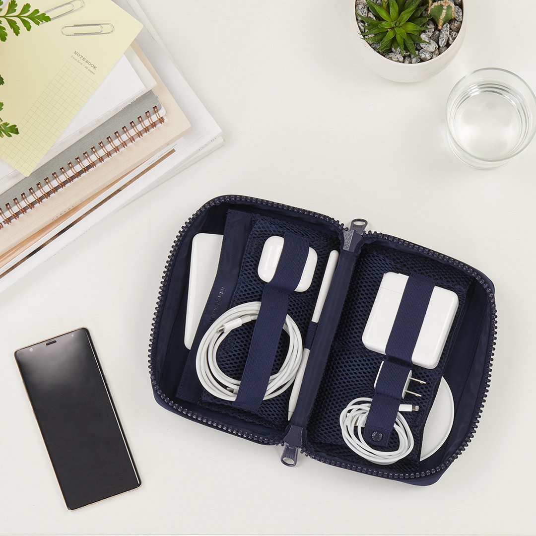 the rectangle pouch in blue, open showing the mesh pockets and straps holding different tech accessories