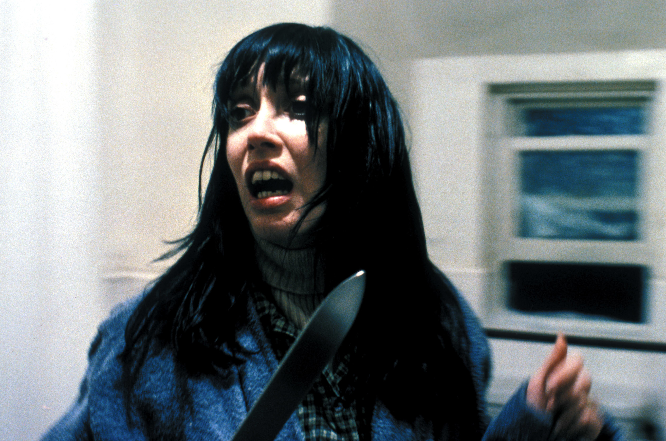 Shelly with a knife looking scared in the film