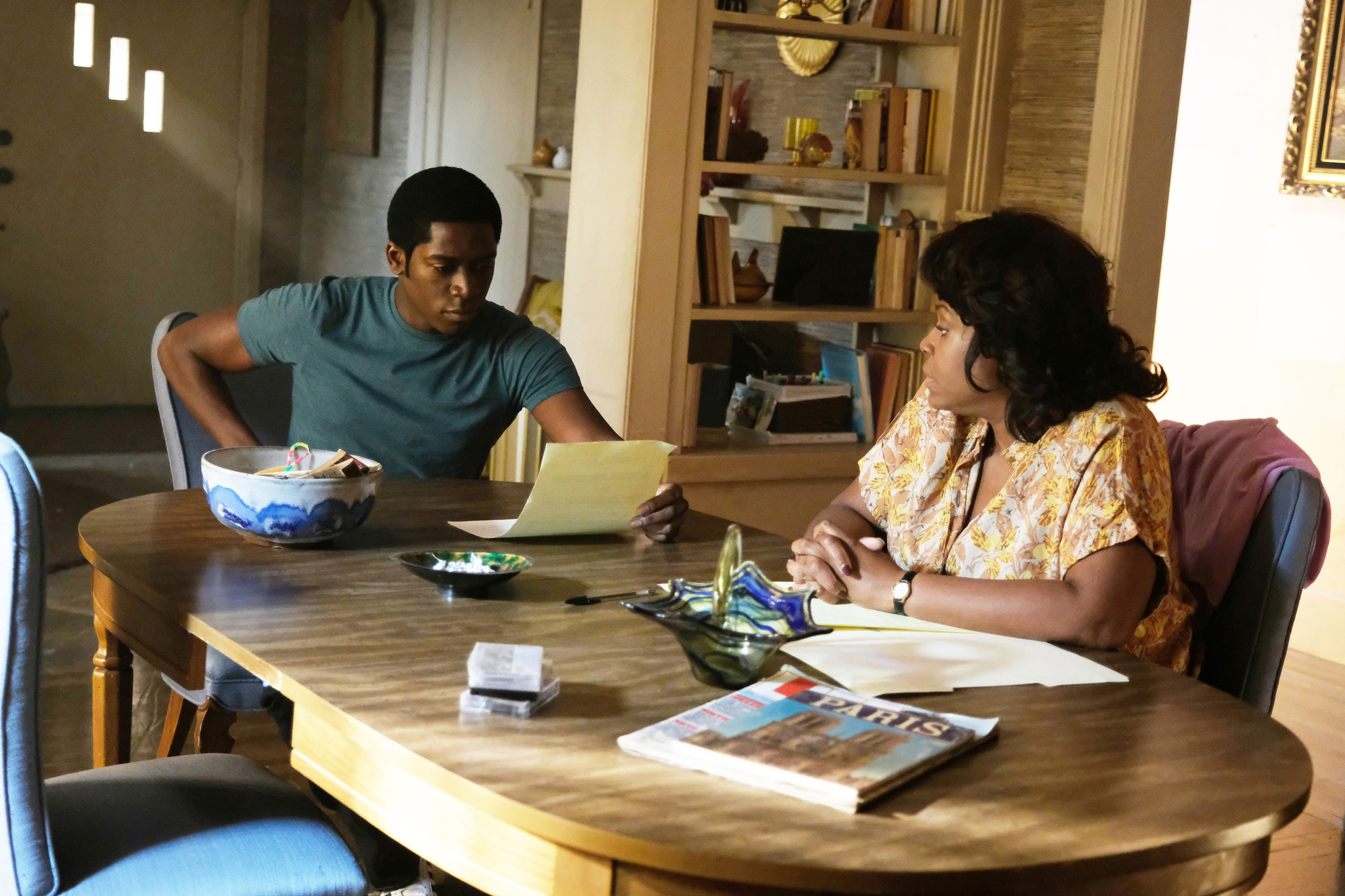 """Damson sitting at a table and reading a piece of paper as an older woman looks on in a scene from """"Snowfall"""""""