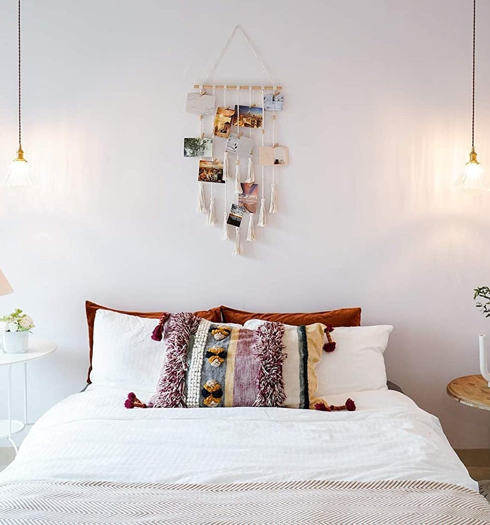 a macrame photo organizer hanging above a bed