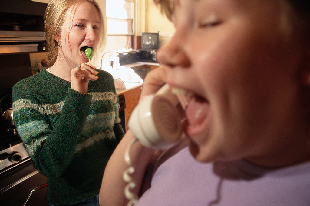 A girl talking on the phone as her friend looks one eating a lollipop