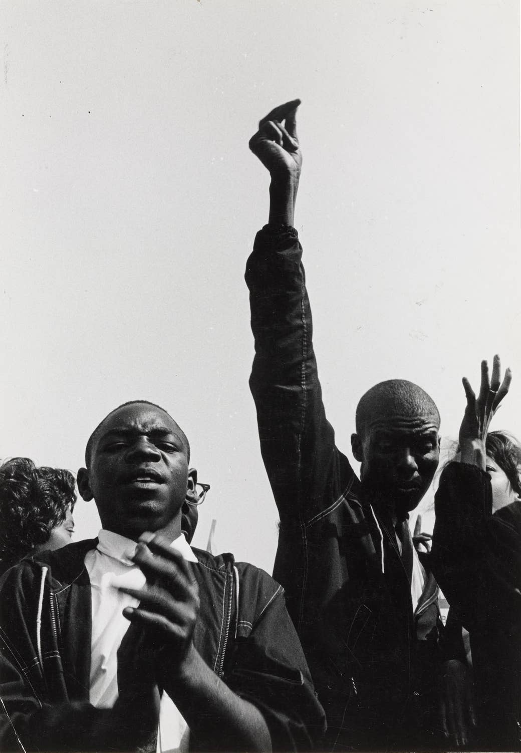 Men clapping and marching, one with his hand in the air