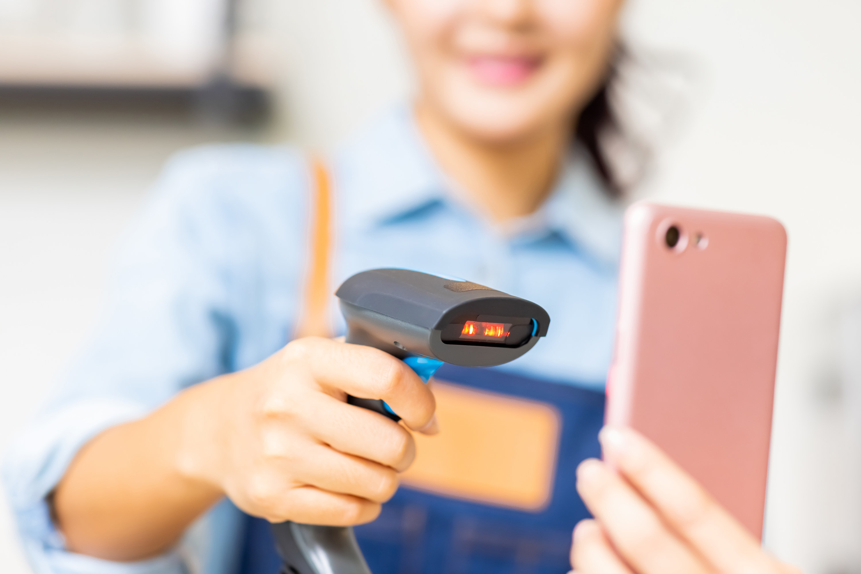 A cashier scanning a person's phone