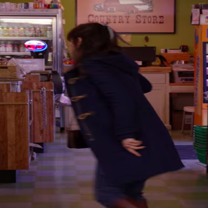 Jess wearing overalls, boots, and a coat