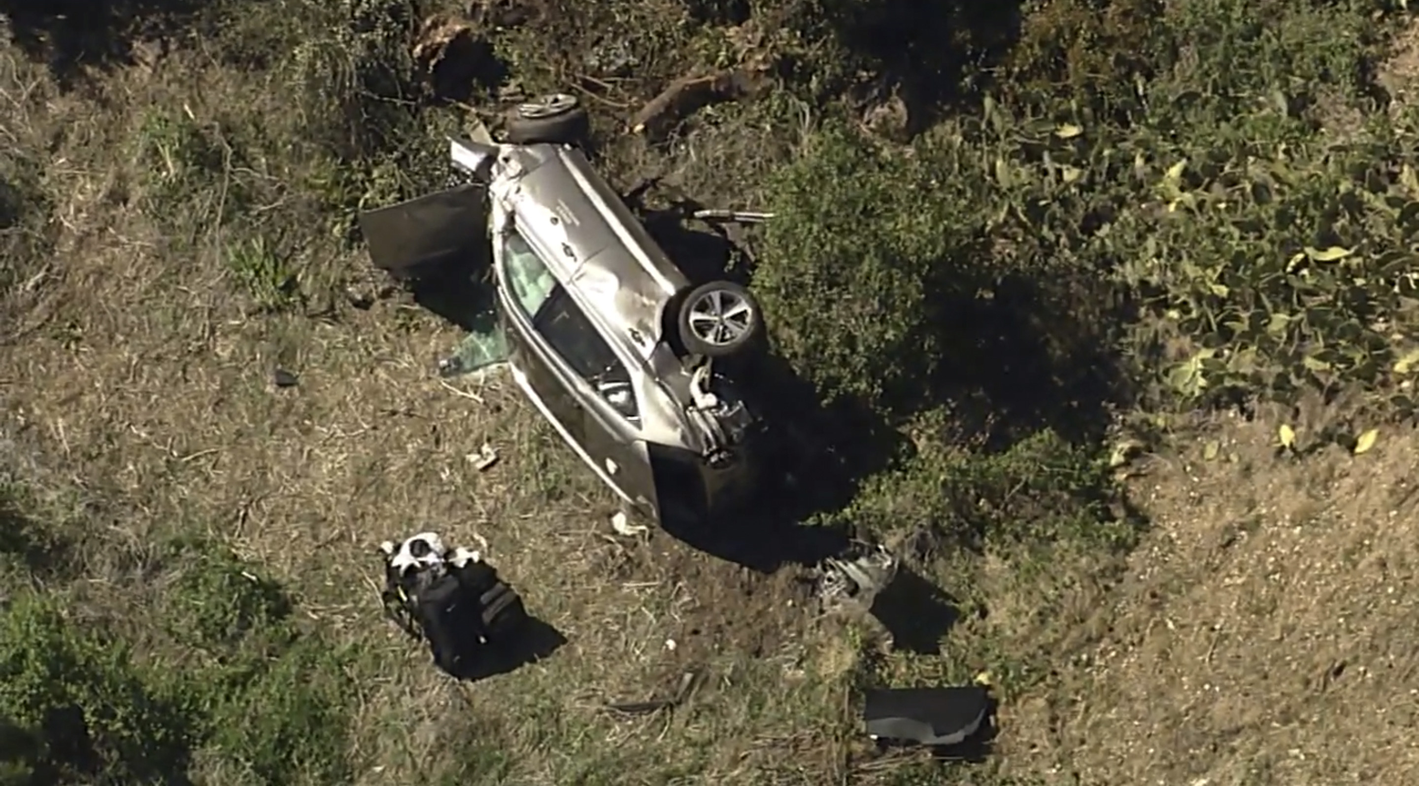 A damaged car rests on its side at the bottom of a hill in this aerial view