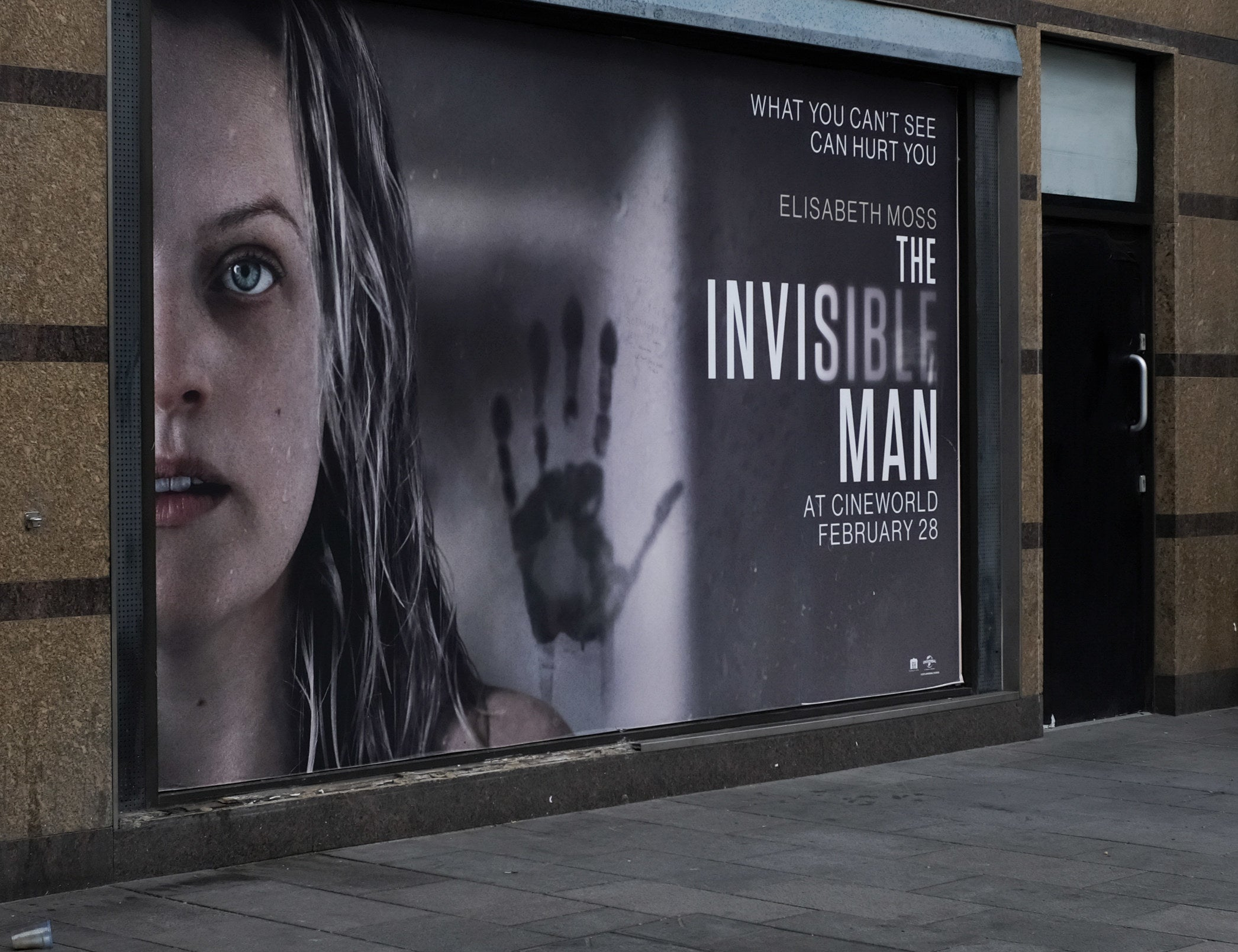 "A large poster for ""The Invisible Man"" on the side of a wall featuring Elisabeth Moss and a handprint"