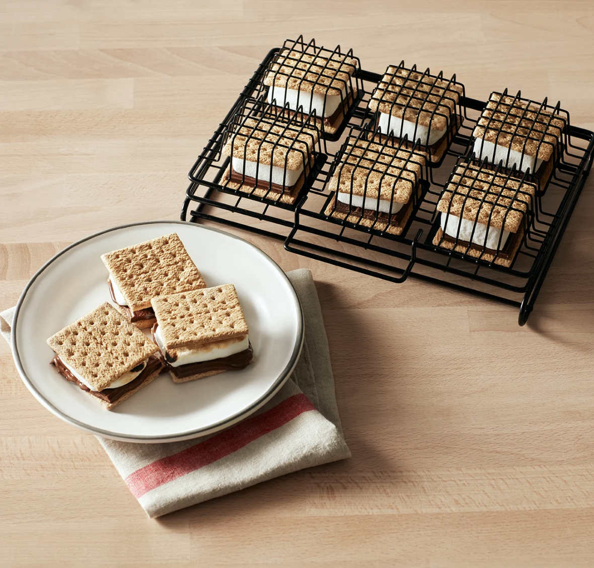 A s'mores grilling rack with six present s'mores in cages next to a plate of cooked s'mores