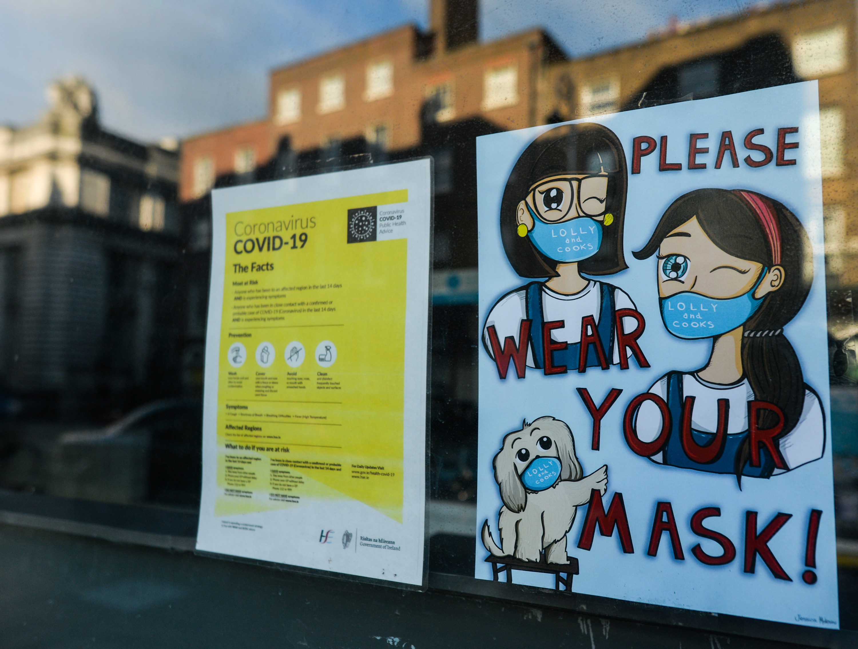 Two signs in a window telling people the facts about COVID-19 and encouraging people to wear masks