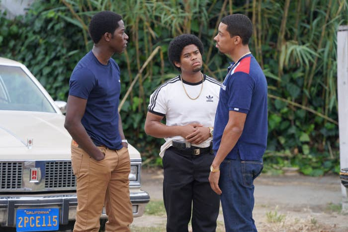 Damson Idris, Isaiah John, Melvin Gregg standing and talking to one another outside in a scene from SnowFall