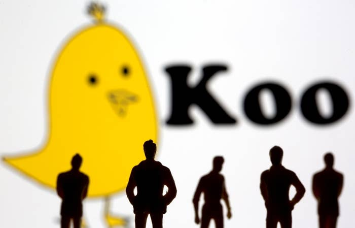 Silhouetted toy figures of people stand in front of the Koo app's logo