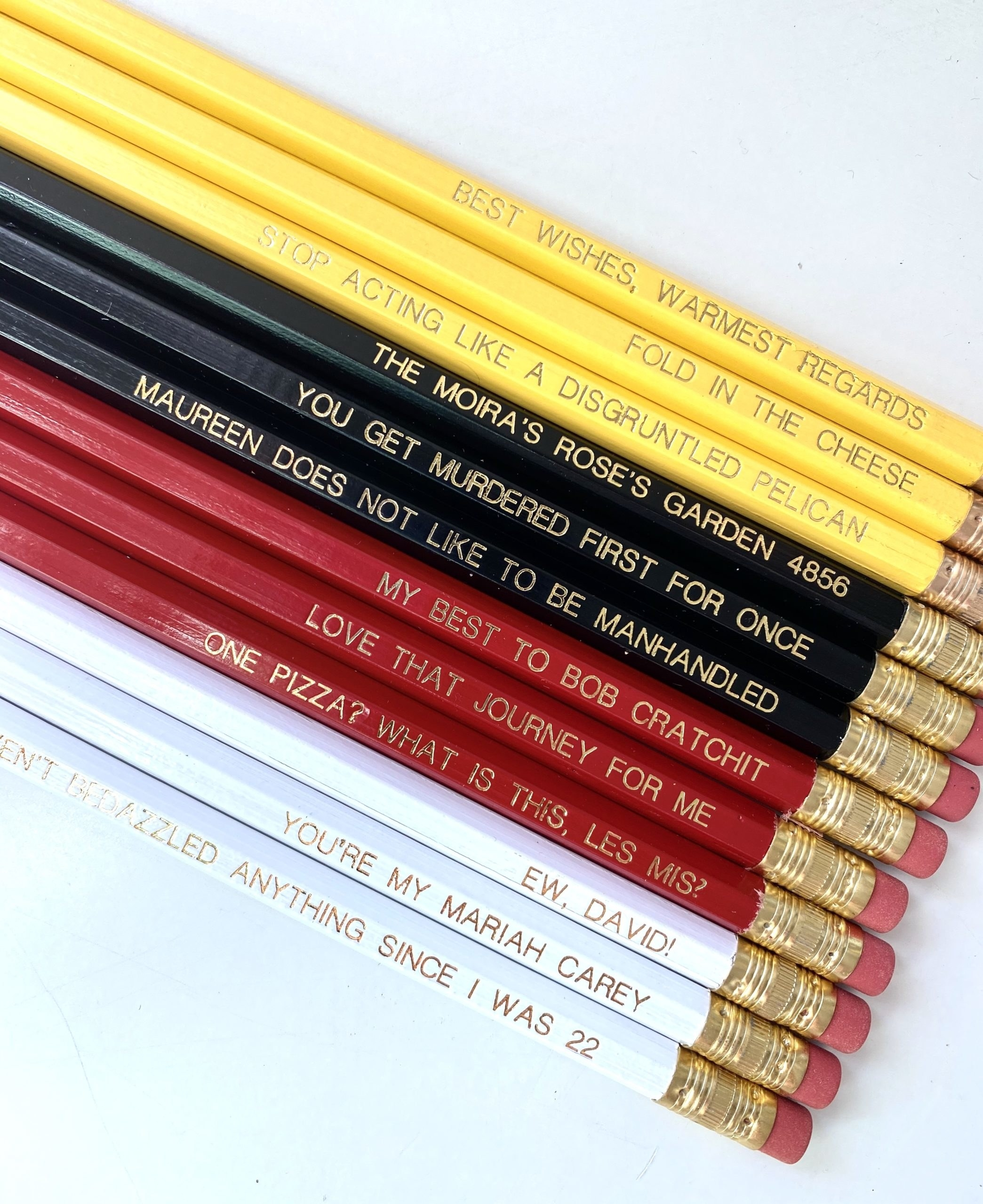 """the set, featuring three yellow, three black, three red, and three white pencils each with a different quote in gold text, from classics like """"Fold in the cheese"""" to more obscure gems like """"I haven't bedazzled anything since I was 22"""""""
