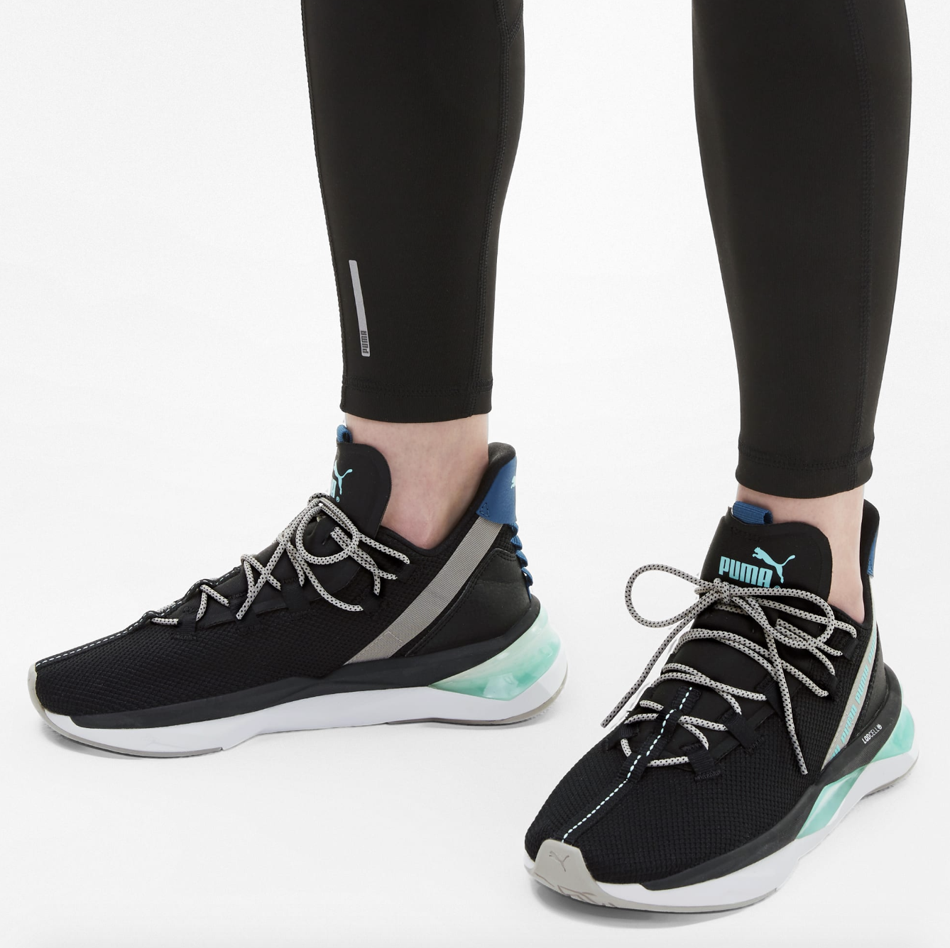 model wears black and green Puma LQDCELL Shatter XT Trail Women's Training Shoes