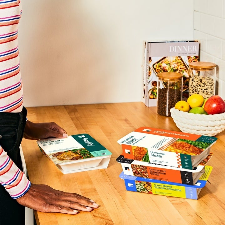 Model placing Freshly meals on kitchen counter