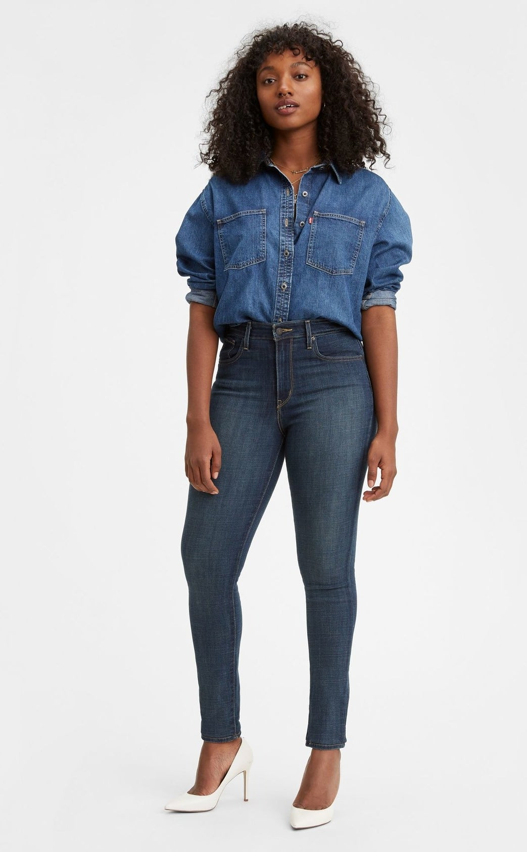 model wearing skinny high rise jeans with a denim shirt and white pumps