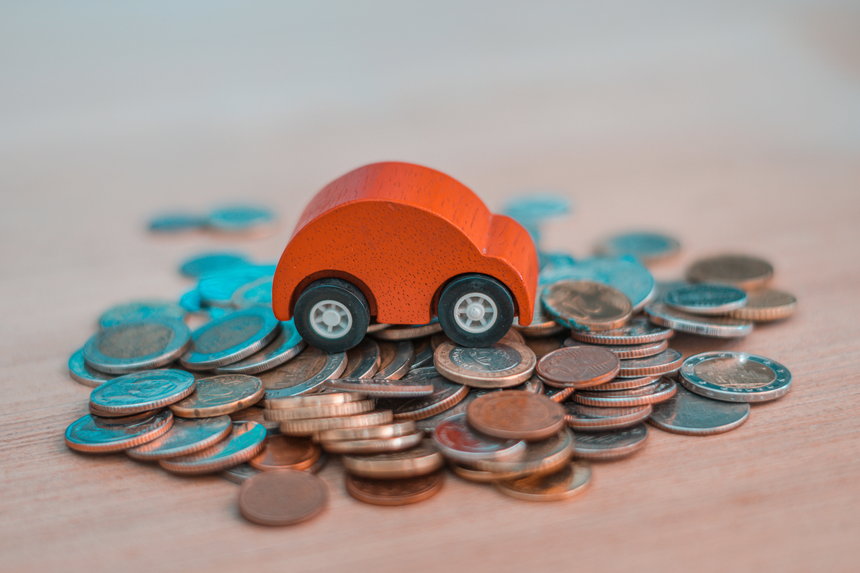 A wooden car on a pile of coins