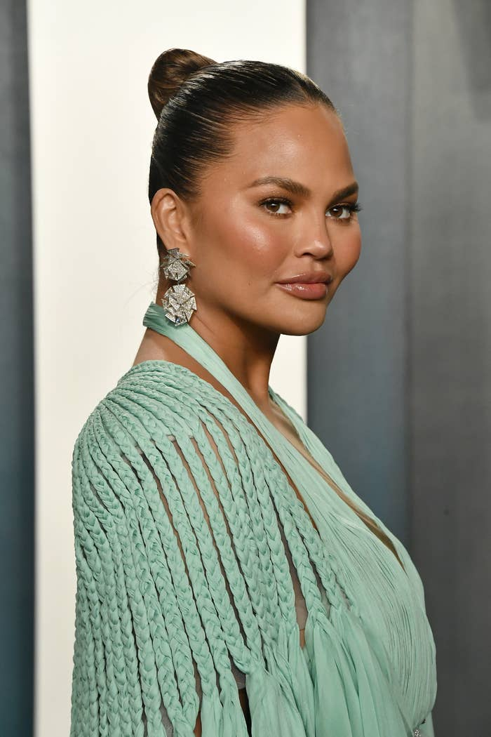 Chrissy Teigen at the 2020 Vanity Fair Oscar Party wearing a braided dress, long earrings, and her hair up in a bun