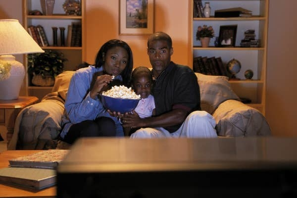 A mom, daughter, and dad sitting on a couch watching a scary movie while eating popcorn