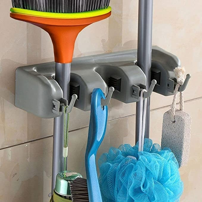 Plastic mop holder with mops and brushes on it.