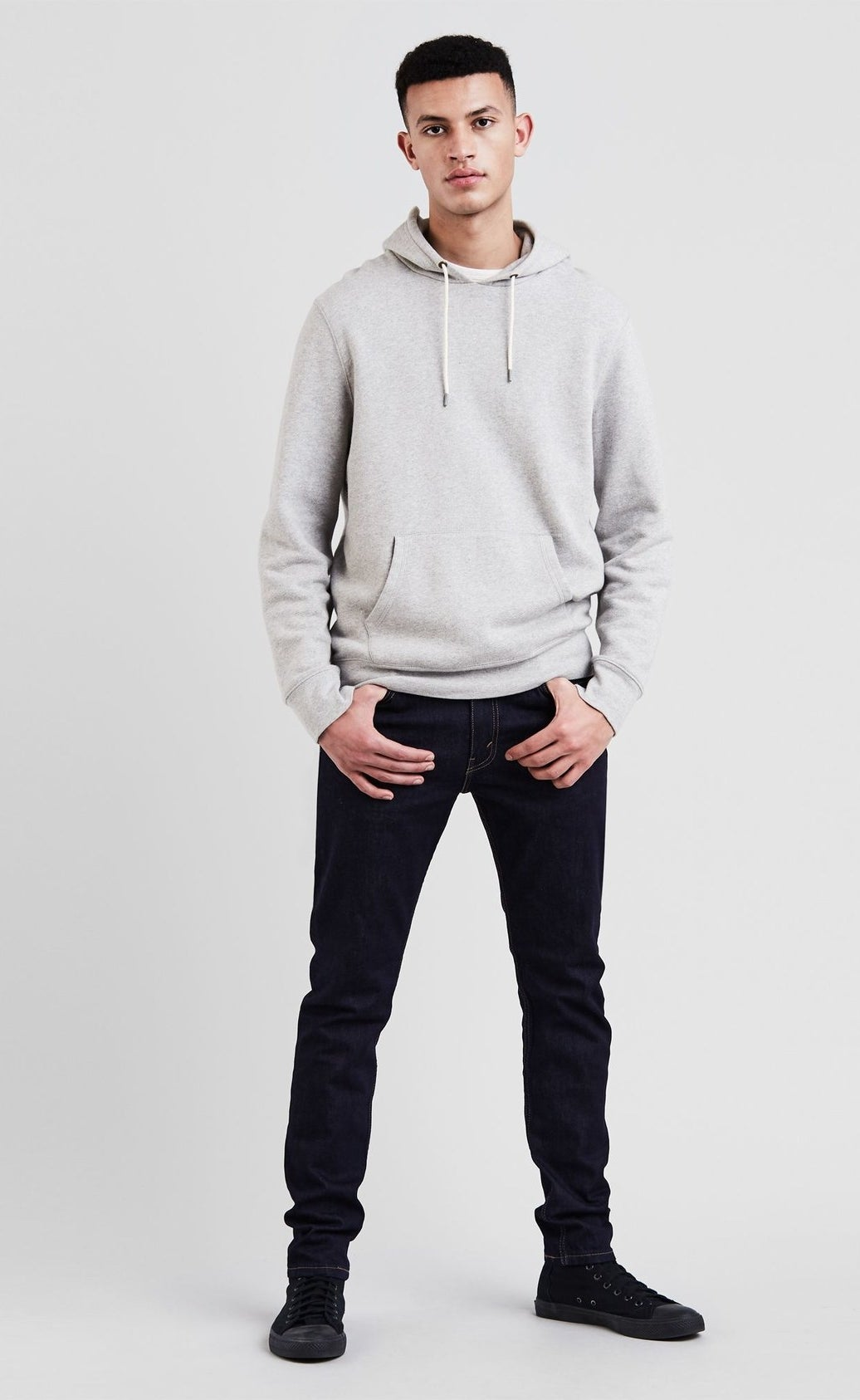 model wearing dark wash jeans with a gray hoodie