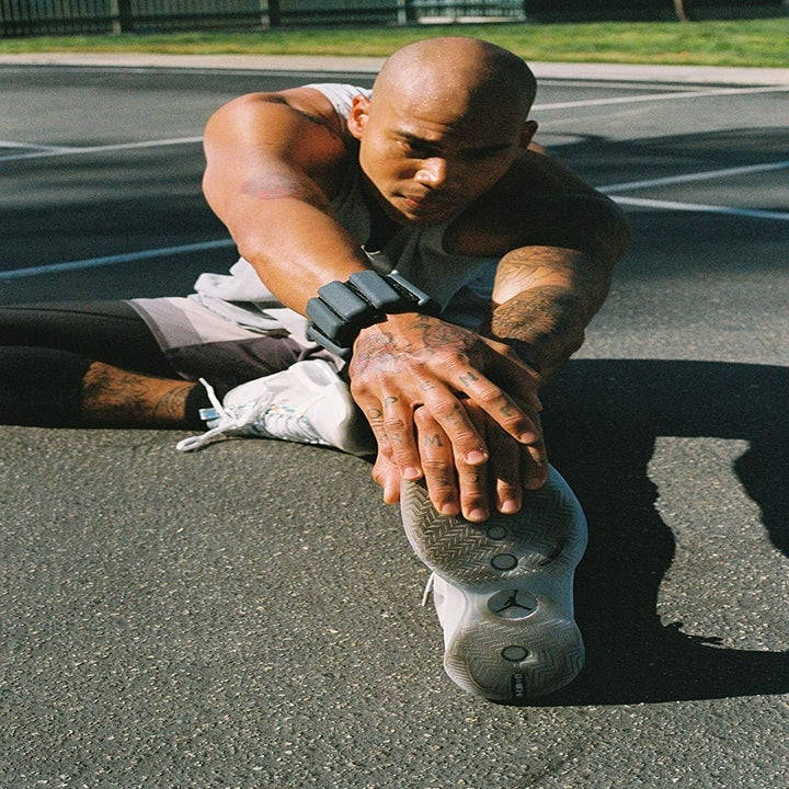 a model wearing the black weight bands on their wrists while stretching