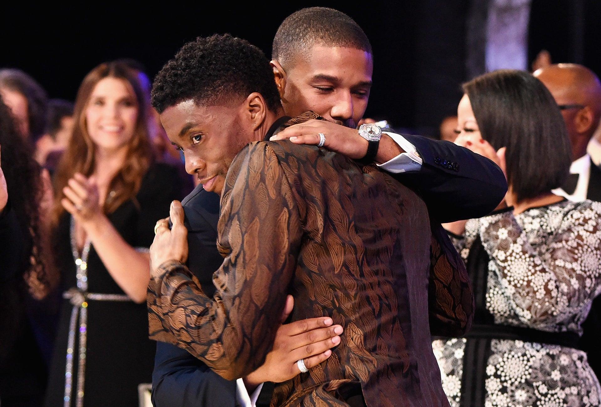 Chadwick and Michael hug onstage