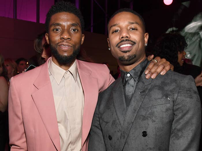 Chadwick puts his arm around Michael at an event