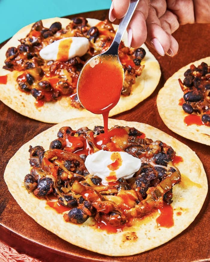 person drizzling hot sauce on Cheesy Black Bean Tostadas