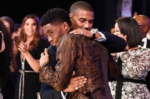 Chadwick and Michael hug on stage