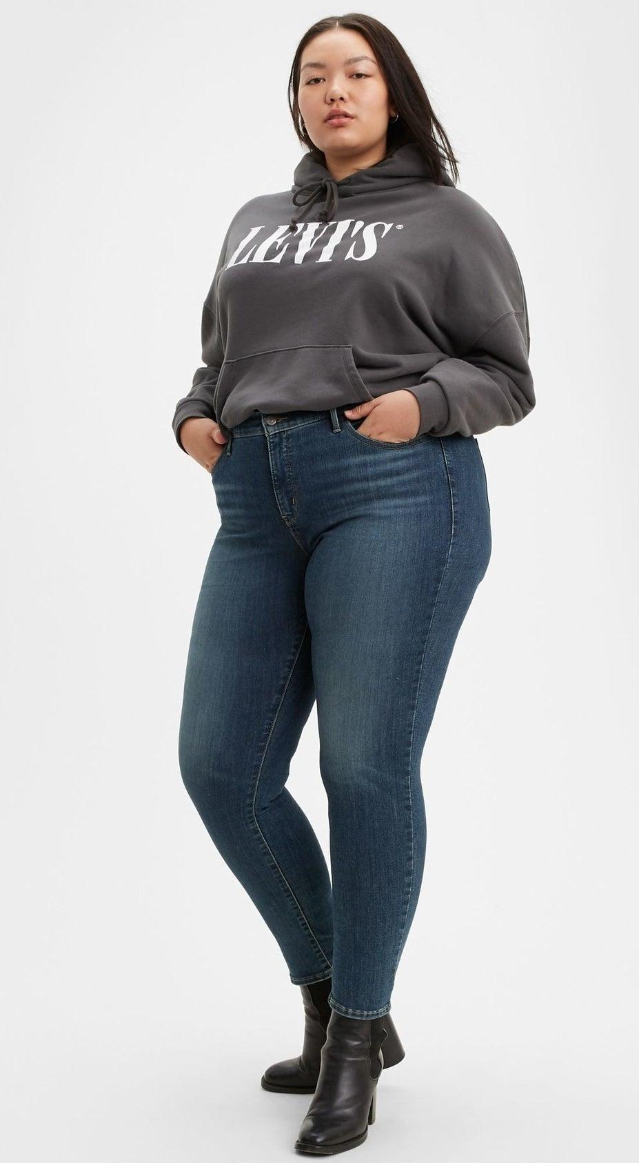 model wearing blue jeans, black booties, and gray hoodie