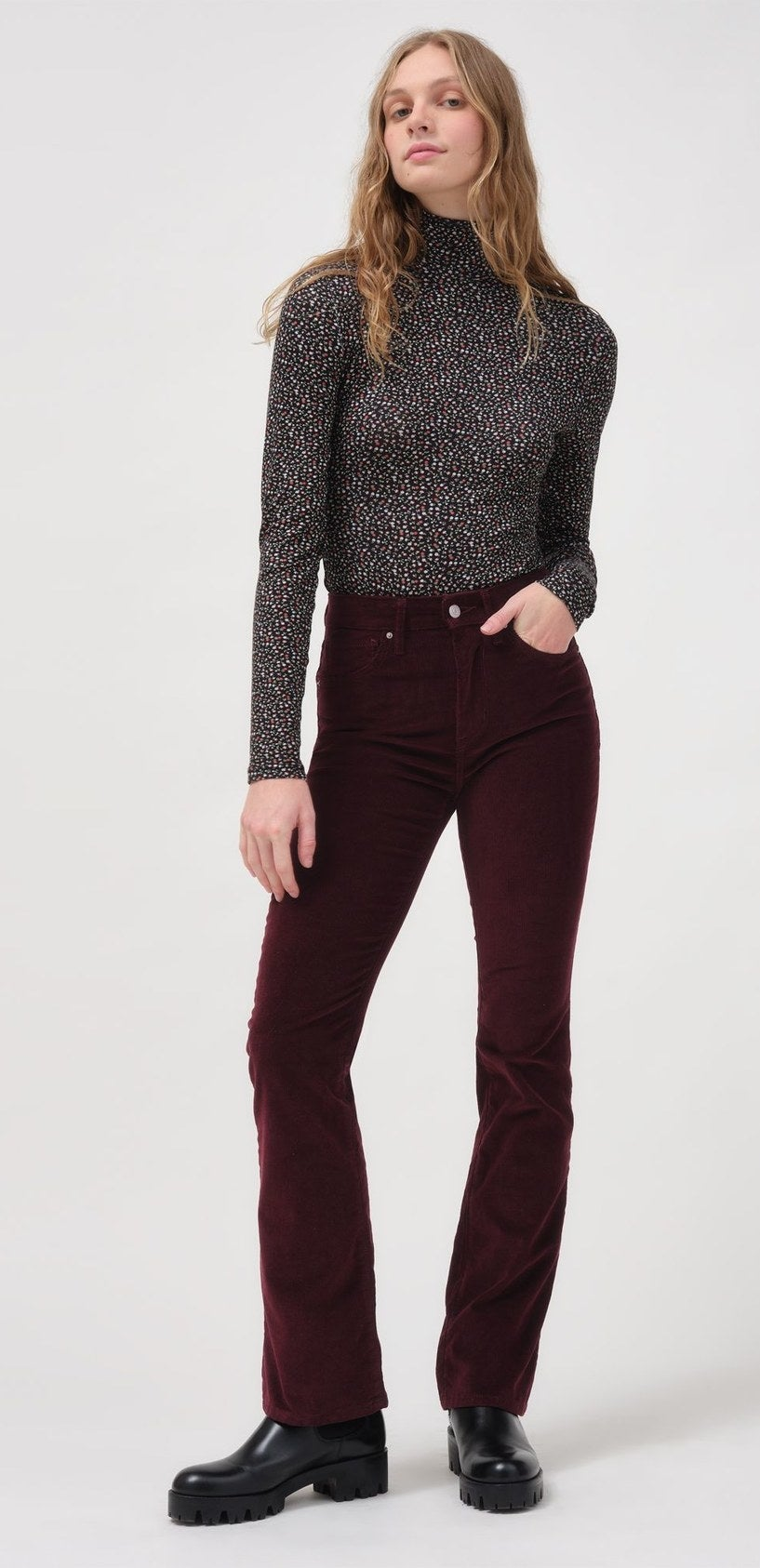 model wearing burgundy corduroy pants with doc martens and a turtleneck