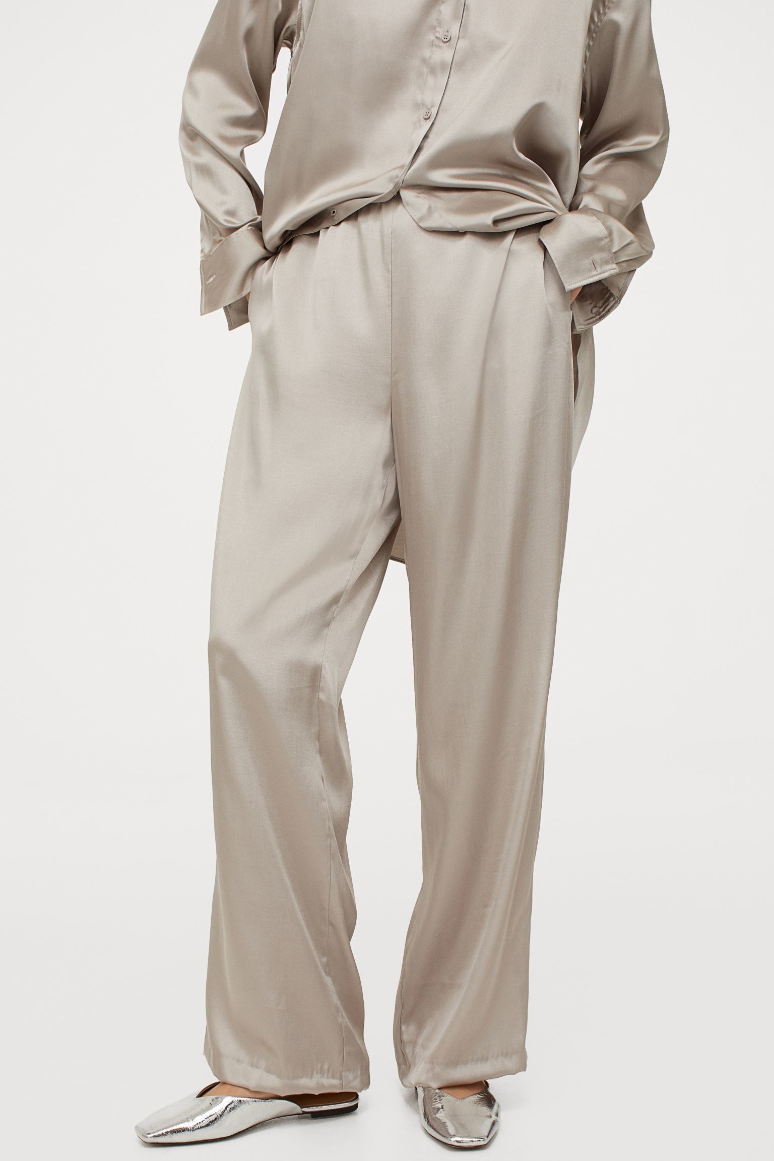 A model wearing the satin pants in taupe