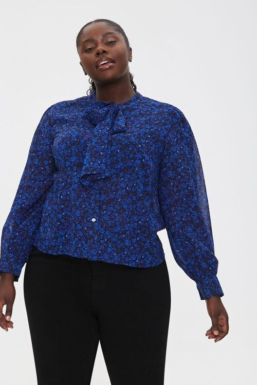 model in blue tie-neck blouse