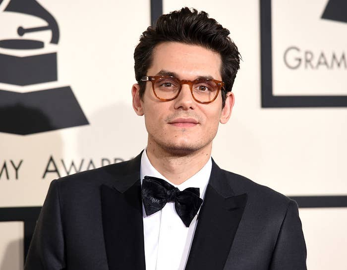 John Mayer wearing a suit, bowtie, and eyeglasses on the Grammy Awards red carpet
