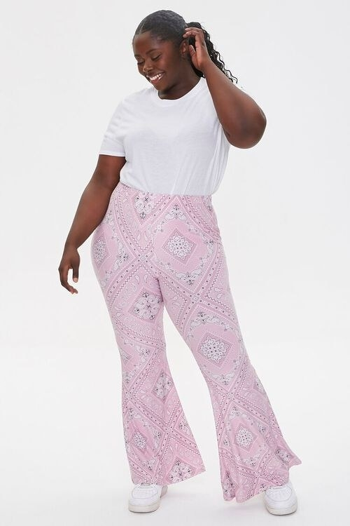 Model wearing the pink flare-legged pants and a white t-shirt