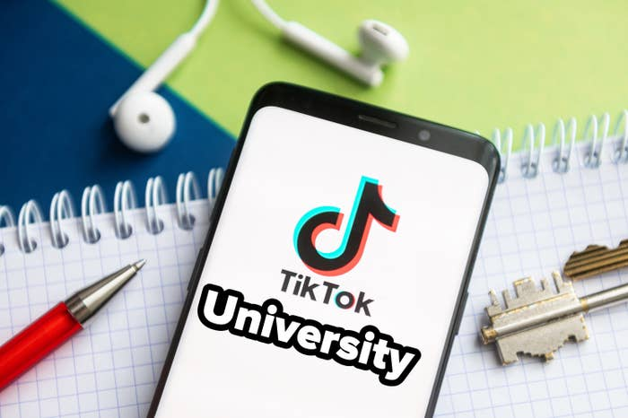 TikTok University on a smartphone which is on top of a notepad next to a pen, key, and earphones