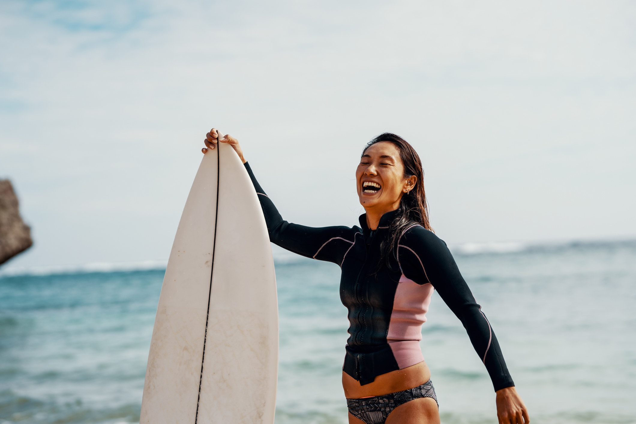 A surfer happily smiling holding a surfboard on the beach