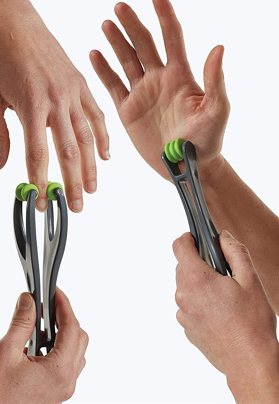 person using the massager on their fingers and wrist
