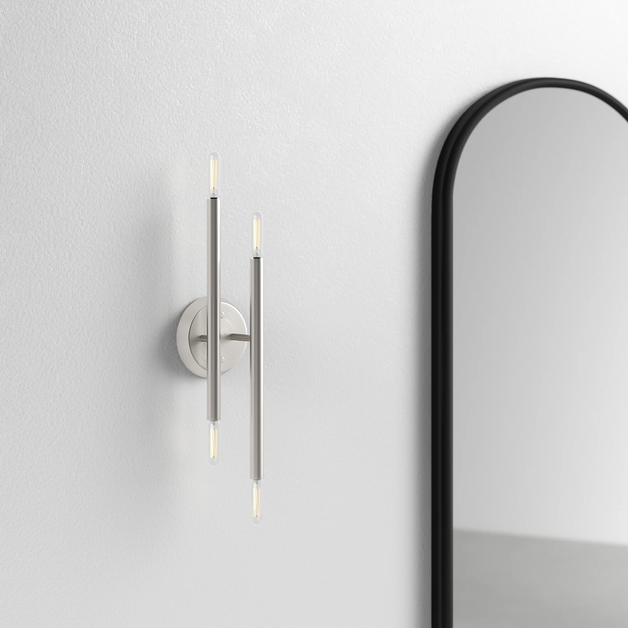 A metal wall sconce with four small lights at the end of two mismatched metal lines installed on a wall next to a mirror