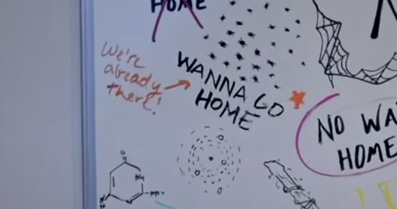 "A close-up of the whiteboard reading ""Wanna Go Home"" and someone drawing an arrow and writing, ""We're already there"""