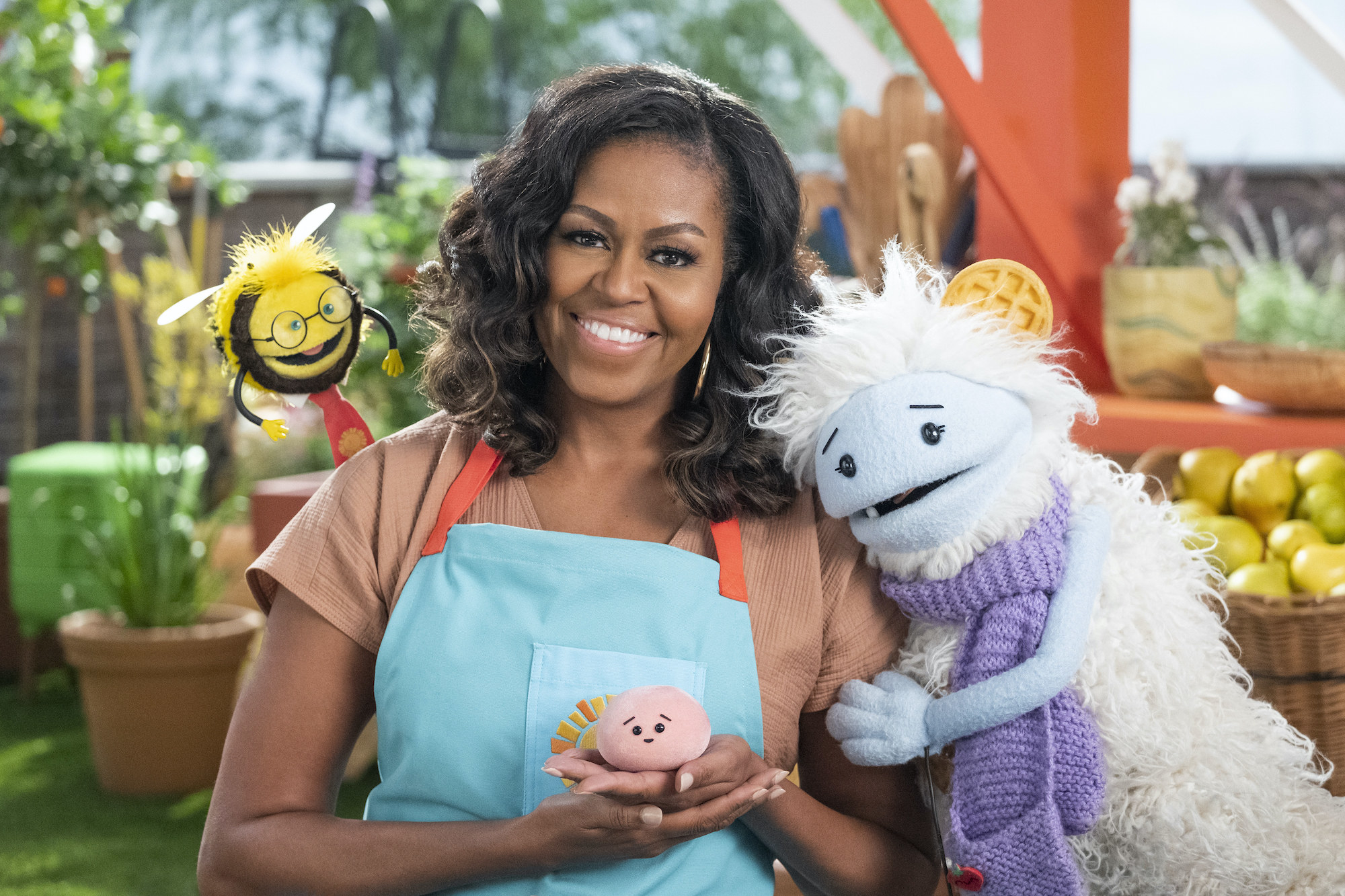 Former First Lady Michelle Obama and two puppets called Waffles and Mochi