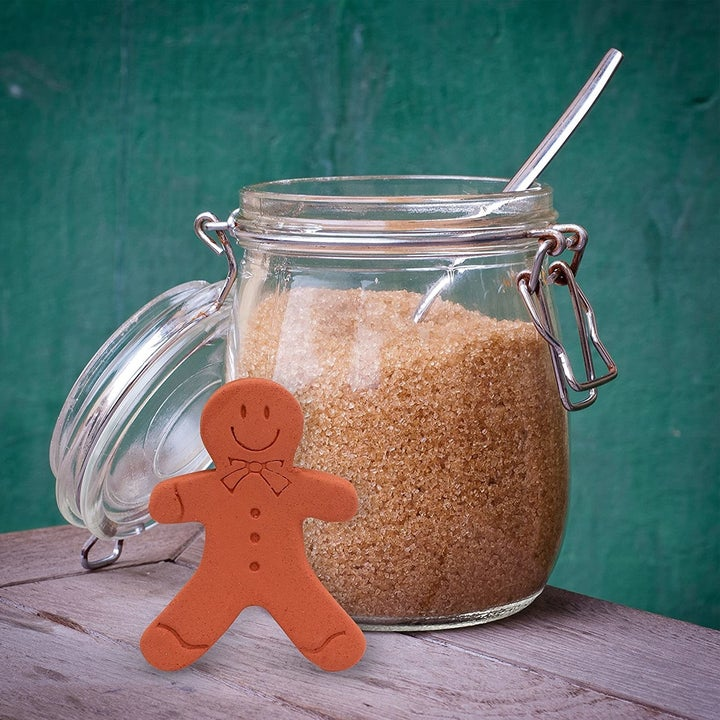 A brown clay gingerbread man figure sitting next to an open glass container of brown sugar