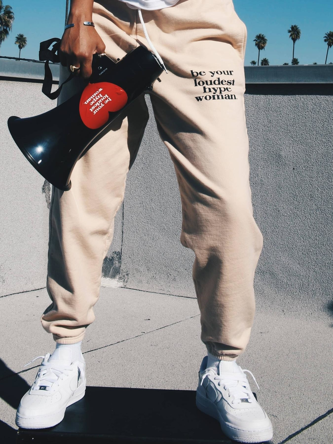 "A model wearing the sweatpants that read, ""Be your loudest hype woman."""