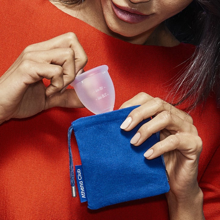 A model holding a clear menstrual cup and putting it in a small blue cloth drawstring bag